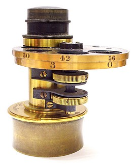The achromatic condenser is marked: Ross, 2053, London. It has two diaphragm disks that can be used in combination where each is controlled by a milled knob. The upper disk has conventional graduated apertures while the bottom disk has apertures for dark field and oblique illumination.